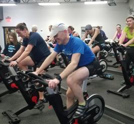 a group of people on spin bikes in a cycle studio